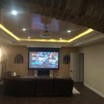Retractable screen in ceiling is lowered for viewing media content